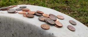 Dozens of pennies rest on top of the unmarked headstone of John Wilkes Booth in the eastern corner of the Booth family plot at Greenmount Cemetery Thursday, May 8, 2013. Booth, who assassinated Pres. Abraham Lincoln in April, 1865, was killed 148 years ago today. Photo by Karl Merton Ferron/staff